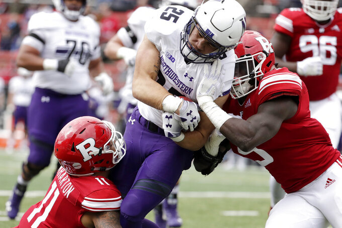 Northwestern running back Isaiah Bowser, center, is tackled by Rutgers defensive back Isaiah Wharton, left, and linebacker Trevor Morris during the first half of an NCAA college football game, Saturday, Oct. 20, 2018, in Piscataway, N.J. (AP Photo/Julio Cortez)