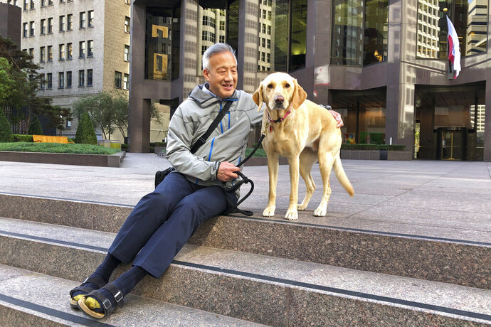 Attorney Ernest Lew sits with his dog, Emma, in a Financial District plaza Friday, Oct. 18, 2019, in San Francisco. California's jobless rate has fallen to a record low 4% and in San Francisco it's dropped under 2%, a level economists once thought impossible to reach.