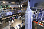Visitors to the Empire State Building pass a scale model of the building as they begin their visit, in New York, Thursday, Oct. 10, 2019. The world-famous observatory atop the Empire State Building has a dizzying new look with floor-to-ceiling, 360-degree windows 102 floors above New York City. (AP Photo/Richard Drew)