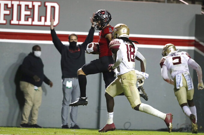 North Carolina State wide receiver Thayer Thomas (5) heads into the end zone in front of Florida State defensive back Travis Jay (18) on a 24-yard touchdown reception during the second half of an NCAA college football game Saturday, Nov. 14, 2020, in Raleigh, N.C. (Ethan Hyman/The News & Observer via AP, Pool)
