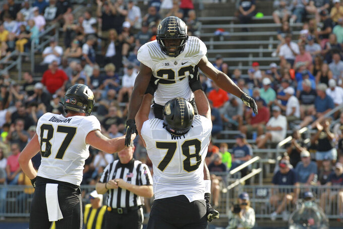Purdue running back King Doerue (22) celebrates his touchdown with offensive lineman Tyler Witt (78) during the first half of an NCAA football game against Connecticut on Saturday, Sept. 11, 2021, in East Hartford, Conn. (AP Photo/Stew Milne)
