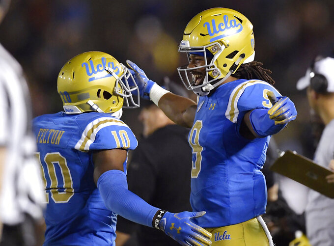 UCLA wide receiver Demetric Felton, left, celebrates with UCLA wide receiver Dymond Lee in the final seconds of an NCAA college football game against Arizona Saturday, Oct. 20, 2018, in Pasadena, Calif. UCLA won 31-30. (AP Photo/Mark J. Terrill)