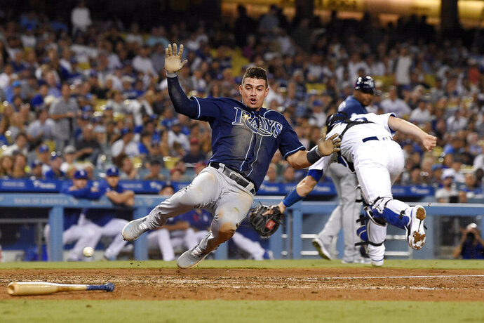 Tampa Bay Rays' Willy Adames, left, scores on a throwing error by Los Angeles Dodgers center fielder Cody Bellinger after a single by Jesus Aguilar, as catcher Will Smith goes after the ball during the sixth inning of a baseball game Wednesday, Sept. 18, 2019, in Los Angeles. (AP Photo/Mark J. Terrill)