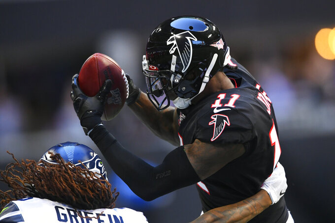 Atlanta Falcons wide receiver Julio Jones (11) works to make the catch Seattle Seahawks outside linebacker Shaquem Griffin (49) during the first half of an NFL football game, Sunday, Oct. 27, 2019, in Atlanta. (AP Photo/John Amis)