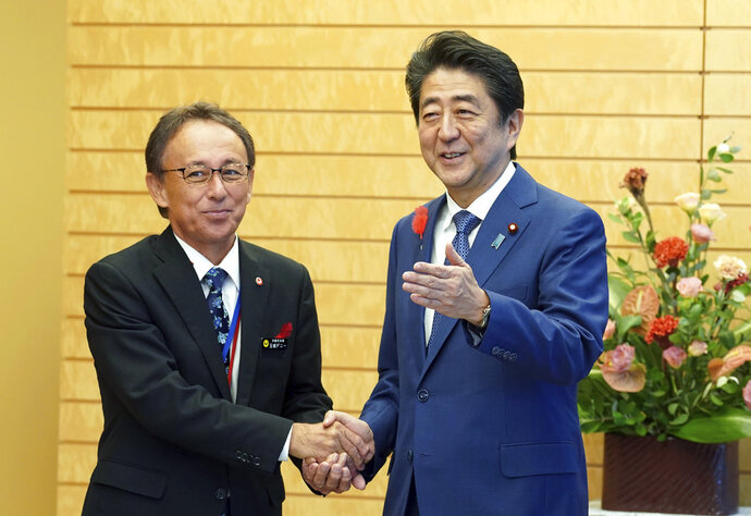 Okinawa Gov. Denny Tamaki, left, and Japanese Prime Minister Shinzo Abe shake hands during a meeting at Abe's office in Tokyo Friday, Oct. 12, 2018. Tamaki won the election for governor at the end of last month, becoming the first Amerasian to lead the southwestern Japanese islands. (AP Photo/Eugene Hoshiko, Pool)