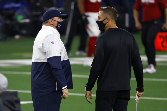 Dallas Cowboys head coach Mike McCarthy, left, and Arizona Cardinals head coach Kliff Kingsbury, right, greet each other on the field during warmups before an NFL football game in Arlington, Texas, Monday, Oct. 19, 2020. (AP Photo/Ron Jenkins)