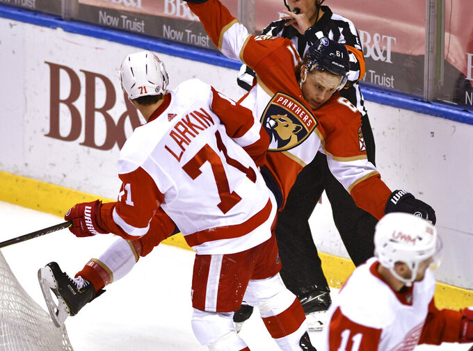Detroit Red Wings center Dylan Larkin (71) gets called for roughing after colliding with Florida Panthers defenseman Riley Stillman (61) during the second period of an NHL hockey game Thursday, April 1, 2021, in Sunrise, Fla. (AP Photo/Jim Rassol)