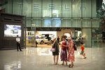 FILE - In this July 5, 2018, file photo, women look at a smartphone outside of a Tesla showroom at an upscale shopping mall in Beijing. Electric car producer Tesla will build its first factory outside the United States in Shanghai under an agreement signed Tuesday, July 10, 2018, becoming the first wholly foreign-owned automaker in China. (AP Photo/Mark Schiefelbein, File)