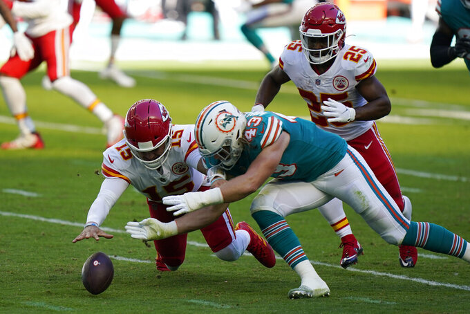 Kansas City Chiefs quarterback Patrick Mahomes (15) and Miami Dolphins outside linebacker Andrew Van Ginkel (43) go after the football after Mahomes fumbled the snap, during the first half of an NFL football game, Sunday, Dec. 13, 2020, in Miami Gardens, Fla. The Chiefs recovered the ball. (AP Photo/Wilfredo Lee)
