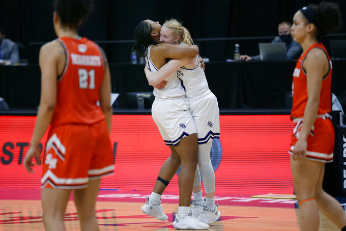 Stephen F. Austin forward Aiyana Johnson and guard Stephanie Visscher, middle, hug as Sam Houston State forward Madelyn Batista (21) and forward Amber Leggett, right, walk to their bench as the buzzer sounds on SFA's win against Sam Houston State after an NCAA college basketball game for the Southland Conference women's tournament championship Sunday, March 14, 2021, in Katy, Texas. (AP Photo/Michael Wyke)
