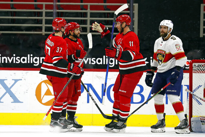 Carolina Hurricanes' Vincent Trocheck (16), center, is congratulated on his goal by teammates Jordan Staal (11) and Andrei Svechnikov (37) with Florida Panthers' Aaron Ekblad (5) nearby during the first period of an NHL hockey game in Raleigh, N.C., Sunday, March 7, 2021. (AP Photo/Karl B DeBlaker)
