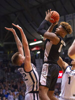 Providence center Nate Watson (0) puts up a shot over the defense of Butler forward Sean McDermott (22) during the second half of an NCAA college basketball game, Tuesday, Feb. 26, 2019, in Indianapolis. Providence won 73-67. (AP Photo/Doug McSchooler)