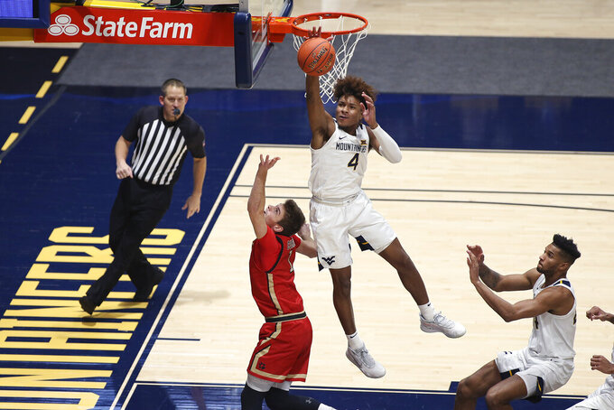 West Virginia guard Miles McBride (4) blocks a shot by Northeastern guard Vito Cubrilo (1) during the second half of an NCAA college basketball game Tuesday, Dec. 29, 2020, in Morgantown, W.Va. (AP Photo/Kathleen Batten)