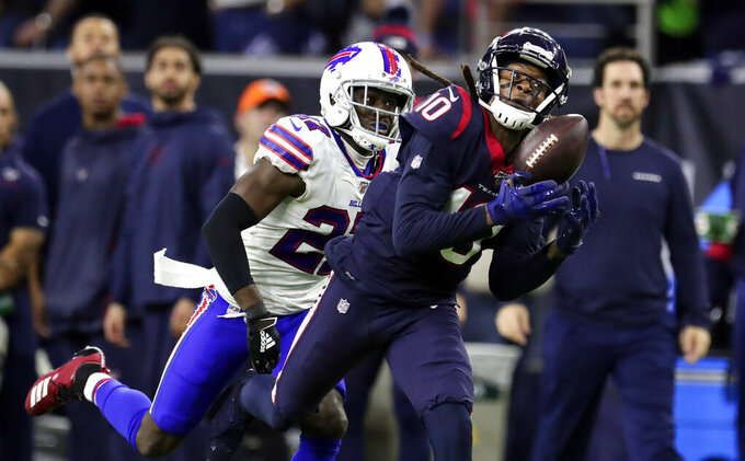 Houston Texans wide receiver DeAndre Hopkins (10) catches a pass for a first down as Buffalo Bills cornerback Tre'Davious White (27) defends during the second half of an NFL wild-card playoff football game Saturday, Jan. 4, 2020, in Houston. (AP Photo/Michael Wyke)
