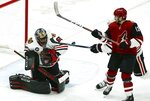 Chicago Blackhawks goaltender Corey Crawford (50) gets some help from Blackhawks defenseman Duncan Keith, back right, on a shot by Arizona Coyotes center Vinnie Hinostroza (13) during the second period of an NHL hockey game Tuesday, March 26, 2019, in Glendale, Ariz. (AP Photo/Ross D. Franklin)