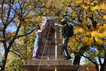FILE - In this Oct. 12, 2020, file photo, demonstrators secure a rope around the centerpiece of a solid stone obelisk before tearing it down in Santa Fe, N.M. At least 160 Confederate symbols were taken down or moved from public spaces in 2020. That's according to a new count the Southern Poverty Law Center shared with The Associated Press. (AP Photo/Cedar Attanasio, File)