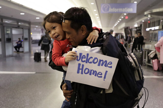 Thy Chea, of Lowell, Mass., center right, originally of Cambodia, hugs his daughter on his arrival at Boston's Logan Airport, Wednesday, Feb. 26, 2020, after getting his green card reinstated last year. Chea is the fourth Cambodian refugee to be allowed back into the country after being deported, and just the first on the East Coast, according to Asian American organizations that have been fighting increased deportations of Southeast Asians under President Donald Trump. (AP Photo/Steven Senne)
