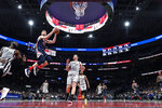 Washington Wizards forward Davis Bertans (42) goes to the basket past San Antonio Spurs forward DeMarre Carroll (77) and center Jakob Poeltl (25) during the second half of an NBA basketball game Wednesday, Nov. 20, 2019, in Washington. The Wizards won 138-132. (AP Photo/Nick Wass)