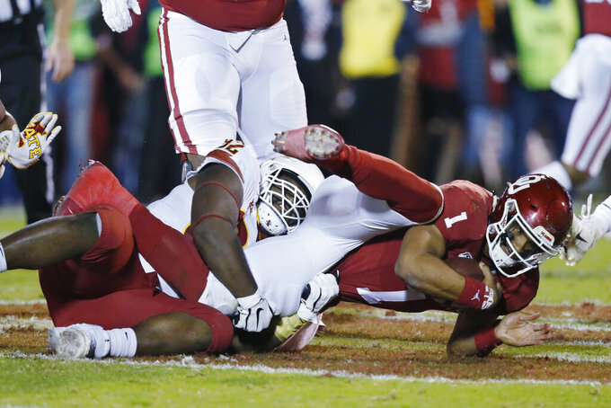 Oklahoma quarterback Jalen Hurts (1) is tackled by Iowa State defensive lineman Jamahl Johnson during the second quarter of an NCAA college football game in Norman, Okla., Saturday, Nov. 9, 2019. (AP Photo/Sue Ogrocki)