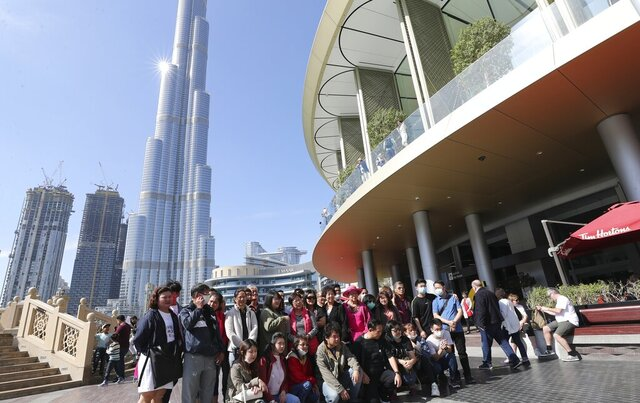 In this Thursday, Jan. 30, 2020, photo, a group of Chinese tourists some of them with face mask pose for a photo under the world's tallest tower, Burj Khalifa, in Dubai, United Arab Emirates. The World Health Organization declared the outbreak sparked by a new virus in China that has been exported to more than a dozen countries as a global emergency Thursday after the number of cases spiked tenfold in a week. (AP Photo/Kamran Jebreili)
