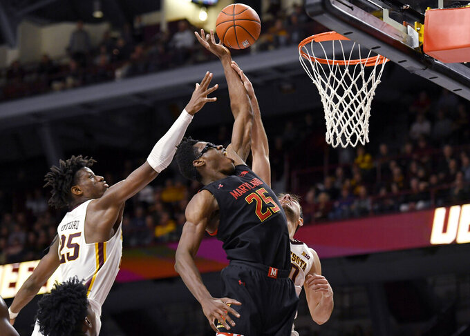 Maryland's Jalen Smith (25) shoots in front of Minnesota's Daniel Oturu (25) and Alihan Demir (30) during the second half of an NCAA college basketball game Wednesday, Feb. 26, 2020, in Minneapolis. Maryland won 74-73. (AP Photo/Hannah Foslien)