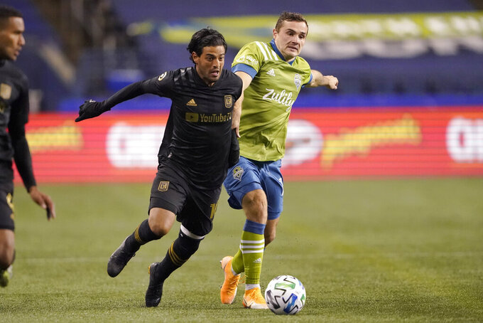 FILE - Los Angeles FC forward Carlos Vela and Seattle Sounders forward Jordan Morris, right, vie for the ball during the second half of an MLS playoff soccer match in Seattle, in this Tuesday, Nov. 24, 2020, file photo. Vela, who had an MLS record 34 goals in 2019, missed the MLS is Back tournament because of his wife's pregnancy and the birth of their child. Then he was hampered by injuries, appearing in only eight games. (AP Photo/Ted S. Warren, File)