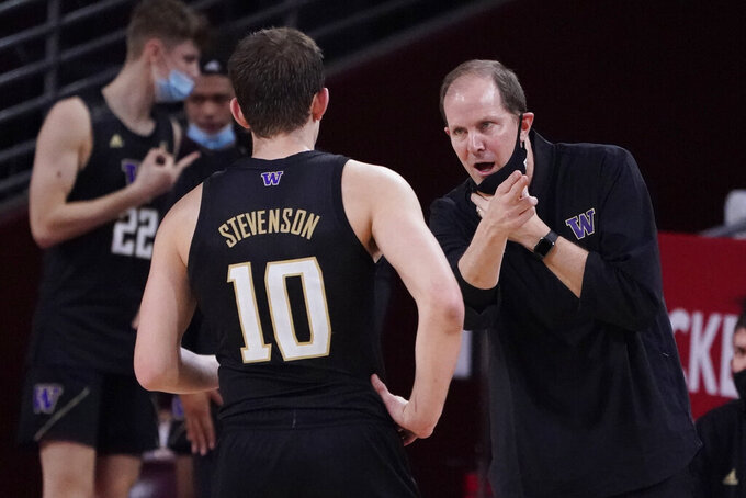 Washington head coach Mike Hopkins, right, talks to guard Erik Stevenson (10) during the second half of an NCAA college basketball game against Southern California Thursday, Jan. 14, 2021, in Los Angeles. (AP Photo/Marcio Jose Sanchez)