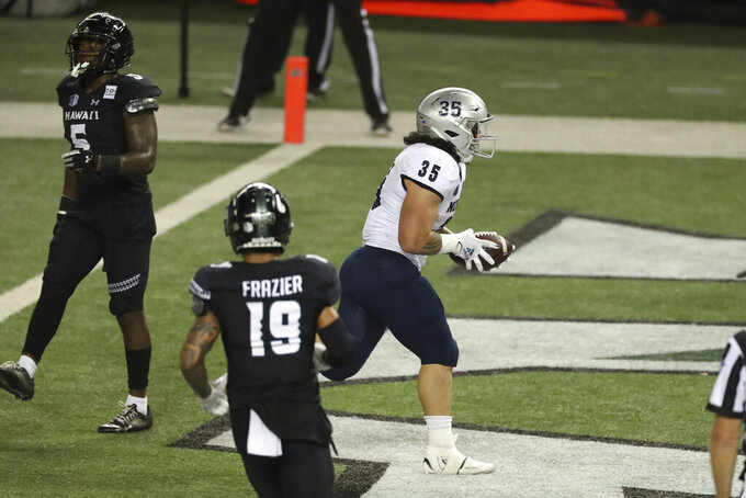 Nevada running back Toa Taua (35) runs into the end zone for a touchdown against Hawaii during the second half of an NCAA college football game Saturday, Nov. 28, 2020, in Honolulu. (AP Photo/Marco Garcia)