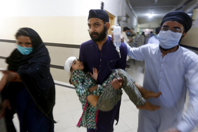 People carry a girl, who was injured in bus and train accident, after receiving initial treatment at a hospital in Sheikhupura near Lahore, Pakistan, Friday, July 3, 2020. A passenger train crashed into a bus carrying Sikh pilgrims at an unmanned railway crossing in eastern Pakistan, police and rescue officials said. (AP Photo/K.M. Chaudary)