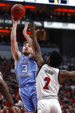 North Carolina guard Andrew Platek (3) shoots over Louisville guard Darius Perry (2) during an NCAA college basketball game Saturday, Feb. 22, 2020, in Louisville, Ky. (AP Photo/Wade Payne)