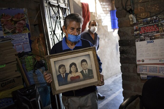 Teodoro Mejia holds a portrait of himself, at right, with his wife Berta Cusi Palomino, moments after funeral home workers removed her body from their home, where according to Mejia she died of COVID-19, in Lima, Peru, Thursday, May 14, 2020. At left in the photo is Berta's brother  Edgar. Peruvian authorities and the Pan American Health Organization are investigating whether the country failed to classify just over 27,000 deaths as caused by the novel coronavirus, a figure that could more than double the country's official death toll from the disease. (AP Photo/Rodrigo Abd)