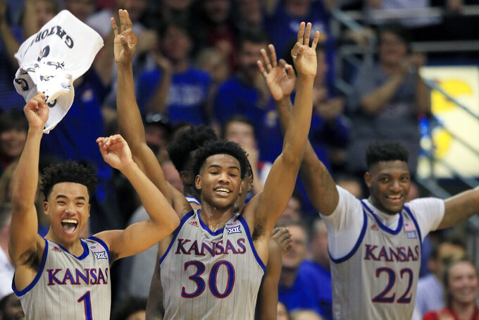 FILE - In this Nov. 15, 2019, file photo, Kansas guards Devon Dotson (1), Ochai Agbaji (30) and forward Silvio De Sousa (22) celebrate a teammate's three-point basket during the second half of an NCAA college basketball game against Monmouth in Lawrence, Kan. Kansas finished the season No. 1 in The Associated Press college basketball poll, receiving 63 of 65 first-place votes from a national media panel Wednesday, March 18, 2020. (AP Photo/Orlin Wagner, File)