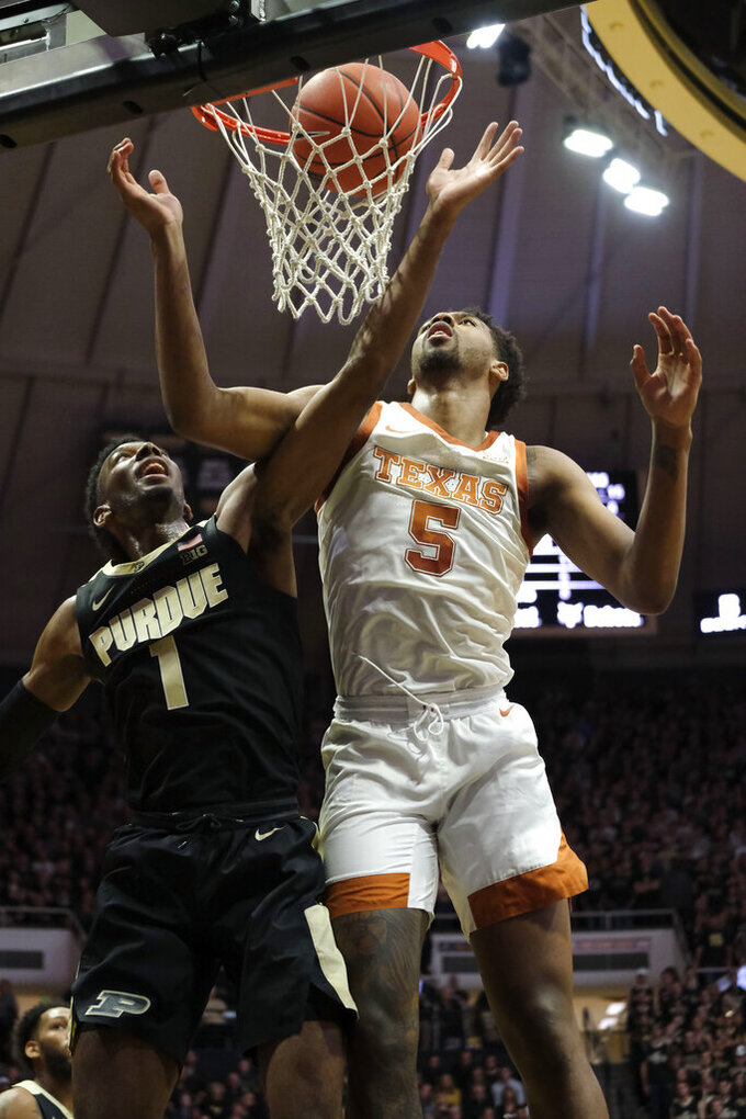 Texas forward Royce Hamm Jr. (5) goes up for a rebound attempt with Purdue forward Aaron Wheeler (1) in the first half of an NCAA college basketball game in West Lafayette, Ind., Saturday, Nov. 9, 2019. (AP Photo/AJ Mast)