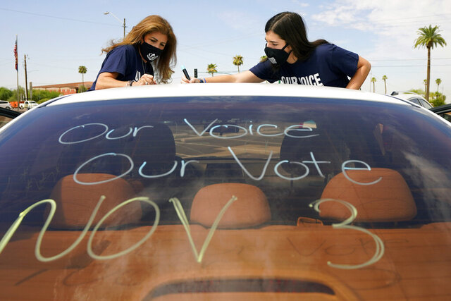 Patricia Santos, left, and her daughter Malia Santos mark their vehicle prior to a car rally Thursday, Aug. 13, 2020, at the Capitol in Phoenix. A coalition of voting rights groups in Arizona have banded together with a lofty goal of getting one million people to vote this November. (AP Photo/Matt York)