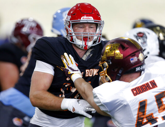 Dayton's Adam Trautman (84) blocks out Minnesota's Carter Coughlin as the North squad practices for the Senior Bowl Thursday, Jan. 23, 2020, in Mobile, Ala. (AP Photo/Butch Dill)