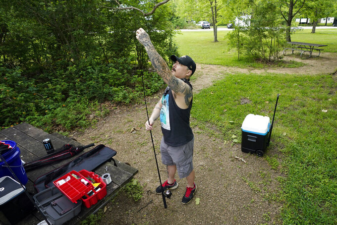 Chris Shin prepares his fishing pole Monday, April 20, 2020, at Sheldon Lake State Park and Environmental Learning Center in Houston. Texas Gov. Greg Abbott has ordered state parks to reopen Monday after being closed due to the COVID-19 outbreak. (AP Photo/David J. Phillip)
