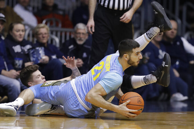 Marquette's Joseph Chartouny (21) makes a pass against Butler's Sean McDermott during the first half of an NCAA college basketball game, Wednesday, Jan. 30, 2019, in Indianapolis. (AP Photo/Darron Cummings)