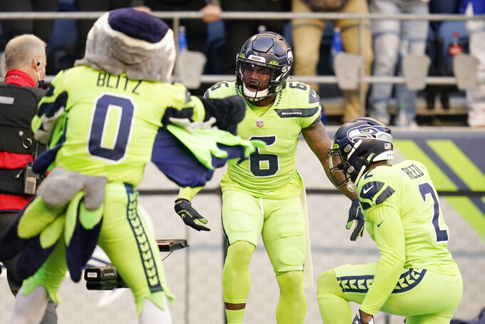 Seattle Seahawks free safety Quandre Diggs (6) celebrates with D.J. Reed (2) and Blitz, the Seahawks mascot, after Diggs intercepted a pass against the Los Angeles Rams during the first half of an NFL football game, Thursday, Oct. 7, 2021, in Seattle. (AP Photo/Elaine Thompson)
