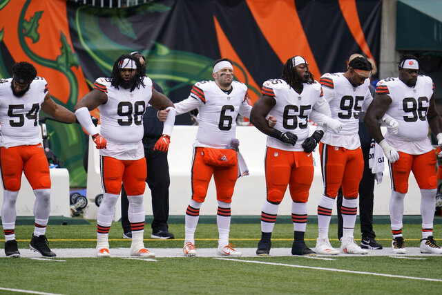 Cleveland Browns quarterback Baker Mayfield (6) locks arms with teammates during the national anthem before an NFL football game against the Cincinnati Bengals, Sunday, Oct. 25, 2020, in Cincinnati. (AP Photo/Michael Conroy)