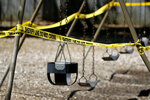 Police tape seals off swings on a closed playground is hopes of slowing the spread of coronavirus Thursday, April 9, 2020, in Rutledge, Ga. (AP Photo/John Bazemore)