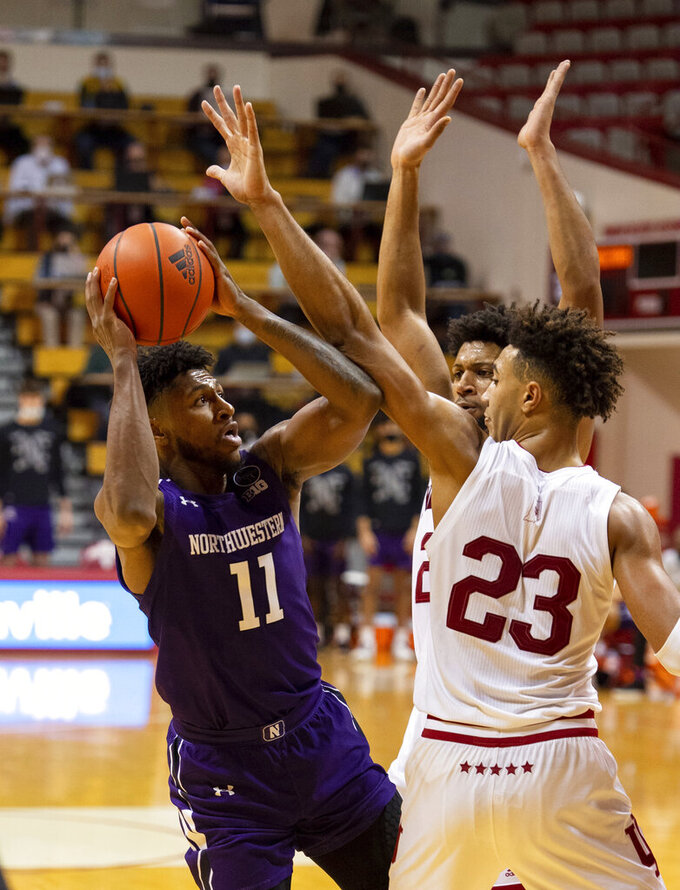 Northwestern guard Anthony Gaines (11) tries to shoot while defended by Indiana guard Armaan Franklin, rear, and forward Trayce Jackson-Davis (23) during the first half of an NCAA college basketball game Wednesday, Dec. 23, 2020, in Bloomington, Ind. (AP Photo/Doug McSchooler)