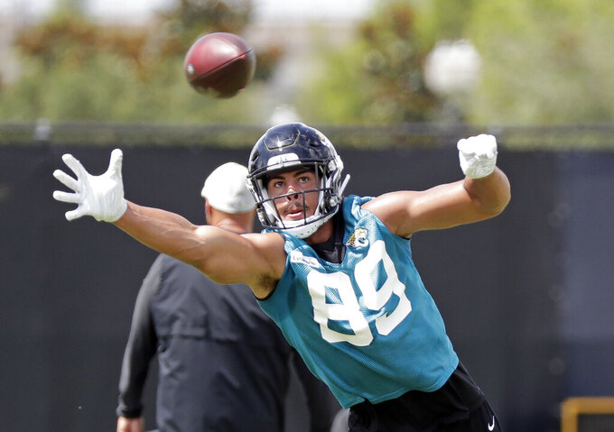 FILE - In this  Friday, May 31, 2019 file photo, Jacksonville Jaguars tight end Josh Oliver (89) reaches for a pass but is unable to make the catch during an NFL football practice in Jacksonville, Fla. A person familiar with negotiations says the Jacksonville Jaguars have traded oft-injured tight end Josh Oliver, a 2019 third-round draft pick who has been limited to four games, to the Baltimore Ravens in exchange for a conditional pick in 2022. (AP Photo/John Raoux, File)