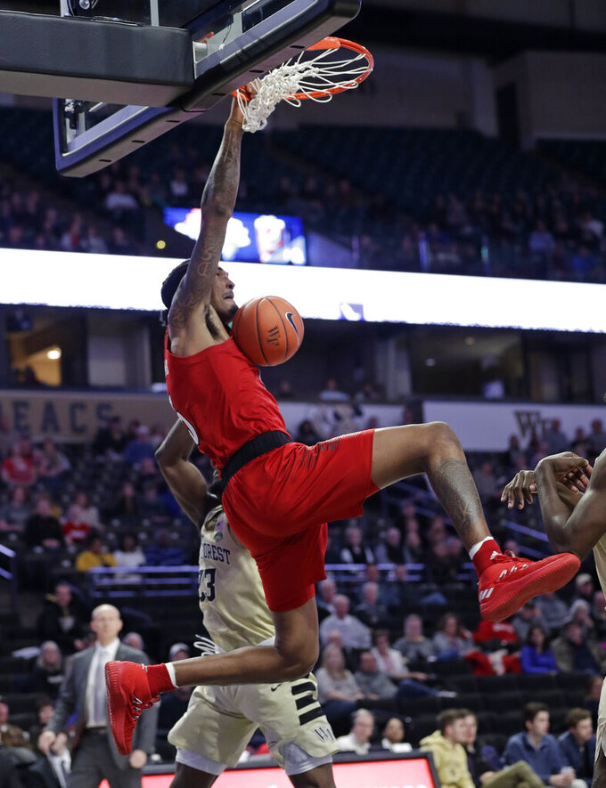 Louisville's Malik Williams (5) dunks next to Wake Forest's Chaundee Brown (23) during the second half of an NCAA college basketball game in Winston-Salem, N.C., Wednesday, Jan. 30, 2019. (AP Photo/Chuck Burton)