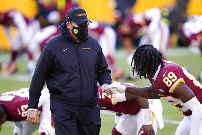 Washington Football Team head coach Ron Rivera greeting wide receiver Cam Sims (89) before the start of an NFL football game against the Carolina Panthers, Sunday, Dec. 27, 2020, in Landover, Md. (AP Photo/Mark Tenally)