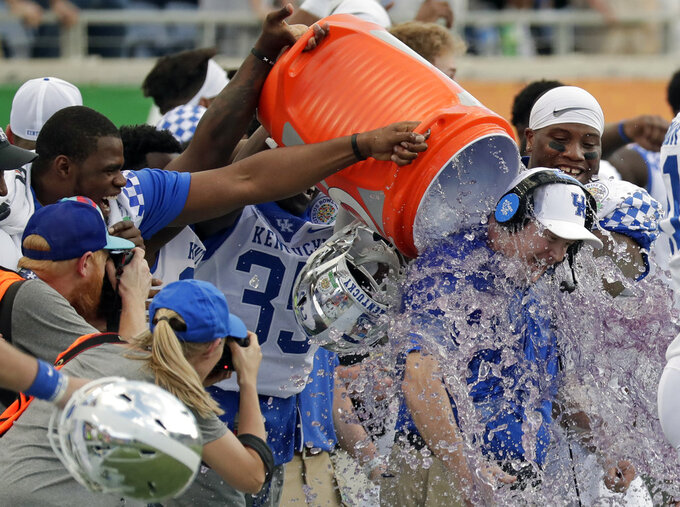 Kentucky head coach Mark Stoops, far right, gets doused with a sports drink after his team defeated Penn State in the Citrus Bowl NCAA college football game, Tuesday, Jan. 1, 2019, in Orlando, Fla. (AP Photo/John Raoux)