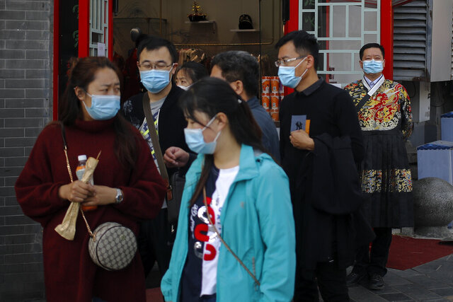 A worker wearing a face mask to help curb the spread of the coronavirus, right, stands watch masked tourists walk by his souvenir shop in Beijing, Sunday, Oct. 25, 2020. With the outbreak of COVID-19 largely under control within China's borders, the routines of normal daily life have begun to return for its citizens. (AP Photo/Andy Wong)