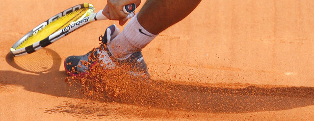 FILE- In this Monday, May 25, 2009, image, Spain's Rafael Nadal slides in the clay as he returns the ball to Brazil's Marcos Daniel during a first round match at the Roland Garros stadium in Paris.  Sliding is one of the keys to success at the French Open, with the ability to glide along the ground to reach shots that others can't, is one of the skills that makes Rafael Nadal so successful on clay courts, although the start of the French Open postponed until September because of the coronavirus. (AP Photo/Christophe Ena, File)