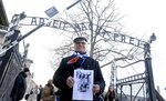 A survivor holds a poster at the former Nazi German concentration and extermination camp Auschwitz, as he attends ceremonies marking the 74th anniversary of the liberation of the camp in Oswiecim, Poland, Sunday, Jan. 27, 2019.(AP Photo/Czarek Sokolowski)