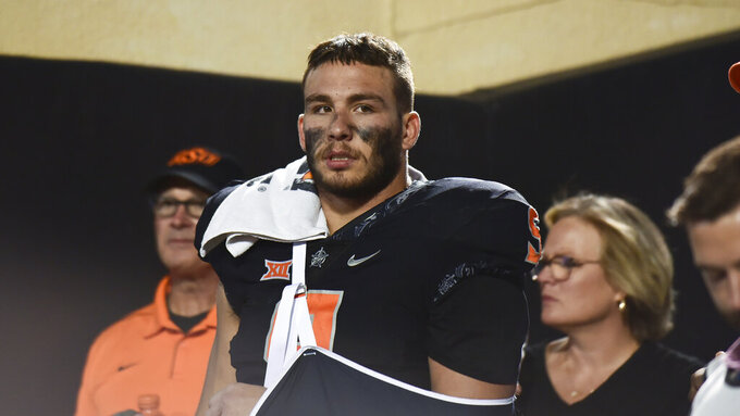 Oklahoma State defensive end Brock Martin (9) stands in the tunnel after becoming injured, during the second half of the NCAA college football game against Kansas State, Saturday, Sept. 25, 2021, in Stillwater, Okla. (AP Photo/Brody Schmidt)
