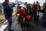 An unidentified passenger is surrounded by the media after she disembarked from the quarantined Diamond Princess cruise ship Wednesday, Feb. 19, 2020, in Yokohama, near Tokyo. Passengers tested negative for COVID-19 started disembarking Wednesday. (AP Photo/Jae C. Hong)